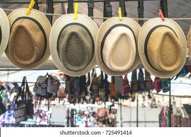 several straw hats in a flea market