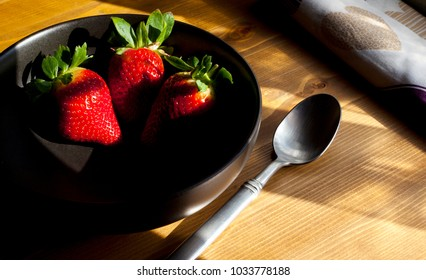 Several Strawberries in Black Bowl on Wooden Surface