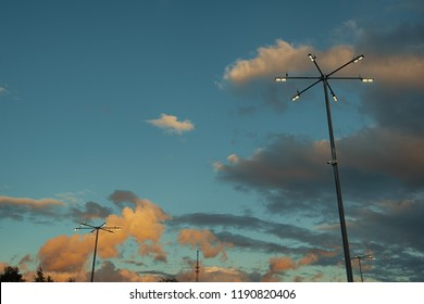 Several street lampposts against a beautiful sky with clouds. Light parking