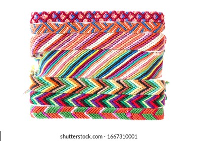 Several striped whicky braided bracelets made with macrame technique. Isolated colorful handmade braided lace
