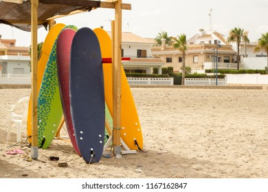 Several surfboards of different colors placed on a wooden structure for storage