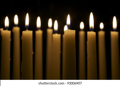 Several tall candles lit in a dark room.