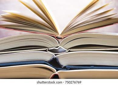 Several textbooks with white sheets opened in the middle