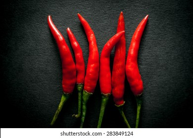 several Thai hot red chili pepper on a black background. Contents of capsaicin pepper determines the sharpness