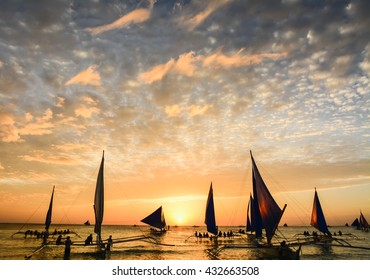 Several tourists are enjoying the spectacular sunset on the island of Boracay seated on typical Philippines boats.
