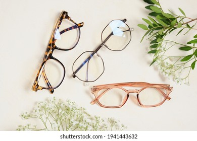 several trendy stylish glasses and flowers on a beige background place copy top view, optics, shop of glasses and frames concept