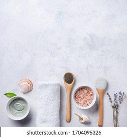 several types of cosmetic clay  green and gray with pink sea salt and lavender on a gray concrete background. Home cosmetologist. Top view, flat lay and copy space.