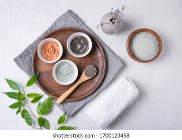 several types of cosmetic clay  pink, green and gray with  lavender on a gray concrete background. Home cosmetologist. Top view, flat lay and copy space.