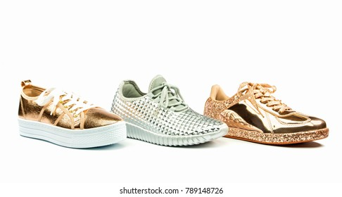 Several types of fashionable sneakers in shiny metallic colors, isolated on white backgroud
