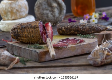 Several variety of traditional Corsican charcuterie with an olive branch and black olives on wooden background.