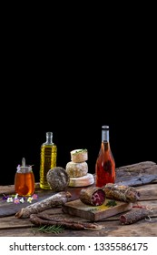 Several variety of traditional Corsican delicatessen and cheese on black background.