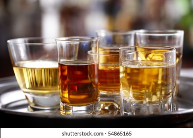 Several various sized shot glasses filled with different whiskeys shot on silver tray in bar setting, space for copy