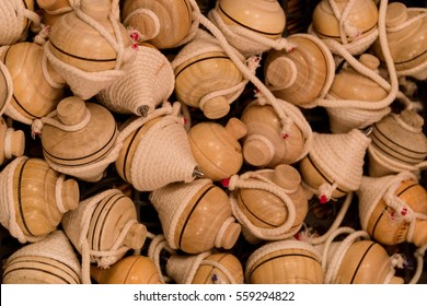 Several vintage wooden spinning top toys with string for sale in a handicrafts store.