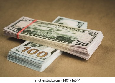 several wads of cash lying on top of each other on a beige background.