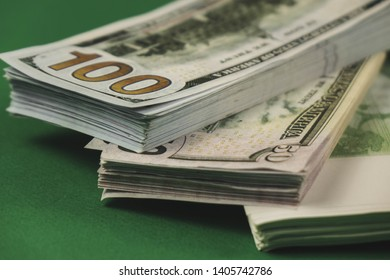 several wads of cash lying on top of each other on a green background