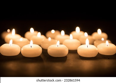 Several white candles with selective focus on a black background