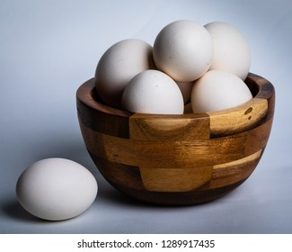 Several white chicken eggs from a backyard chicken coop in a wooden bowl on a white background.