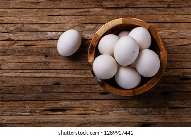 Several white chicken eggs from a backyard chicken coop in a wooden bowl on a wooden board in an overhead shot.
