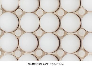 Several white eggs in an egg carton.