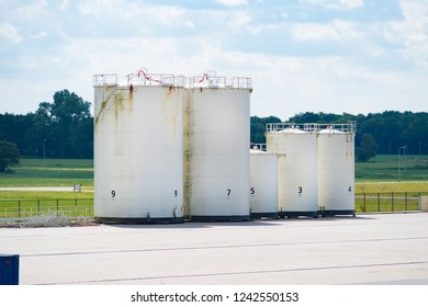 several white storage tanks of a container terminal