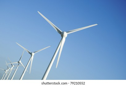Several wind turbines against a blue sky