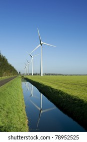 Several wind turbines in a green field and reflection in the water