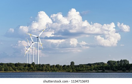 Several wind turbines stand in front of a huge cloud formation at the shore of a lake, warm summer weather