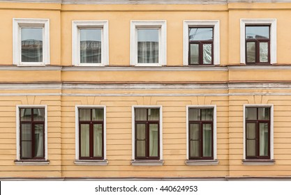 Several windows in a row on facade of urban apartment building front view, St. Petersburg, Russia