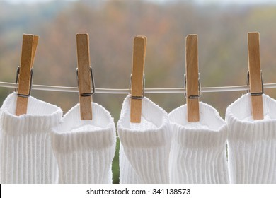 Several wooden clothespins holding a white white athletic socks on an outdoor laundry line.