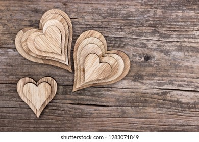 Several wooden hearts on an old wooden background
