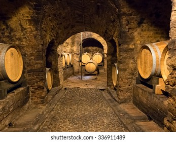 Several wooden wine barrels stocked in an ancient medieval cellar located in Neive, town in Langhe region