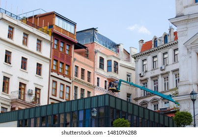 Several workers in building cradle are restoring facade of old building in historic city center. Mediterranean style, Greek architecture. Turkey, Istanbul, Taksim, Beyoglu - August 2019.