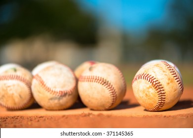Several worn baseballs on pitchers mound close up