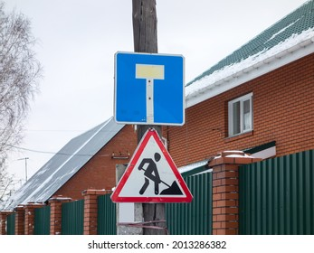 """several worn-out used battered road signs """"dead end"""" and """"repair work"""", square and triangular, mounted on metal plate with bright reflective paint applied to attract attention near the brick house"""