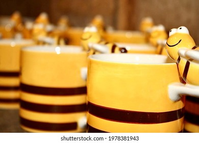 Several yellow and black ceramic tiled cups are arranged on the handle, a statue of a cute smiling bee.