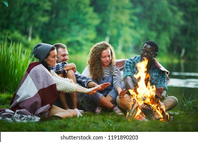 Several young backpackers sitting by campfire by waterside and warming their hands
