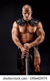 Severe barbarian in leather costume with sword. Portrait of balded muscular gladiator. Studio shot. Black background.