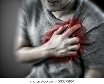 Severe heartache, man suffering from chest pain, having heart attack or painful cramps, pressing on chest with painful expression.radial blur effect focus on chest.