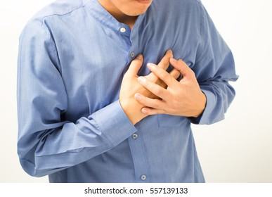 Severe heartache, man suffering from chest pain, having heart attack or painful cramps, pressing on chest with painful expression.