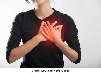 Severe heartache, woman suffering from chest pain, having heart attack or painful cramps,pressing on chest with painful expression.