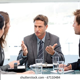 Severe manager talking to his team at a table during a meeting