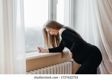 Severe pain in a pregnant woman standing near the window. Pregnancy