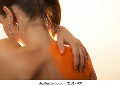 Severe Shoulder Pain A young woman holds her back in pain! The area on the shoulder is highlighted to symbolize the pain.