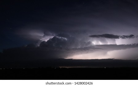 A severe thunderstorm is illuminated by lightning as stars shine overhead in western Nebraska on a summer night.