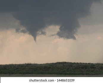 A severe thunderstorm's wall cloud produces a funnel cloud over a countryside hill in tornado alley.