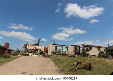 Severe tornado damage to homes and belongings is very apparent in the light of a beautiful blue sky sunny day.