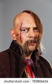 Severe warrior Russian Cossack, face in scars, bald. Bled blood. Saber in sheath. Close-up portrait.