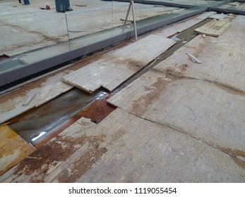 Severe water damage on industrial hardwood floor.
