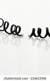 Severed black coiled telephone cord on a reflective white surface, vertical format with copyspace conceptual of a breakdown in communication