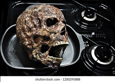 Severed head, human head burnt cooking in a frypan on the stove special effects makeup Halloween prop